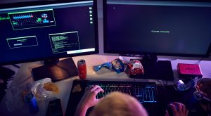 Male Teenage Hacker Sitting In Front Of Computer Screens Bypassing Cyber Security